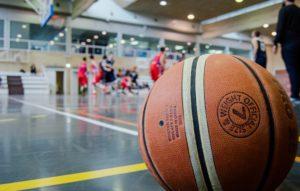 Kuvassa koripallo etualalla ja taustalla pelataan koripalloa liikuntahallissa.
