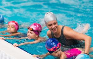Uimaopettaja opettamassa lapsia altaassa uimaan.